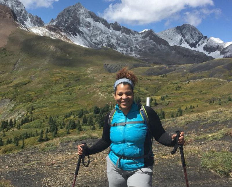 A black woman wearing a turquoise colored vest smiles at the camera. She is standing in a high mountain valley with a hiking pole in each hand and sharp, snow-covered mountain peaks behind her.
