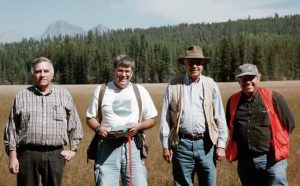 Four mature men dressed in jeans and T-shirts stand side by side in a large meadow with forest trees in the background.