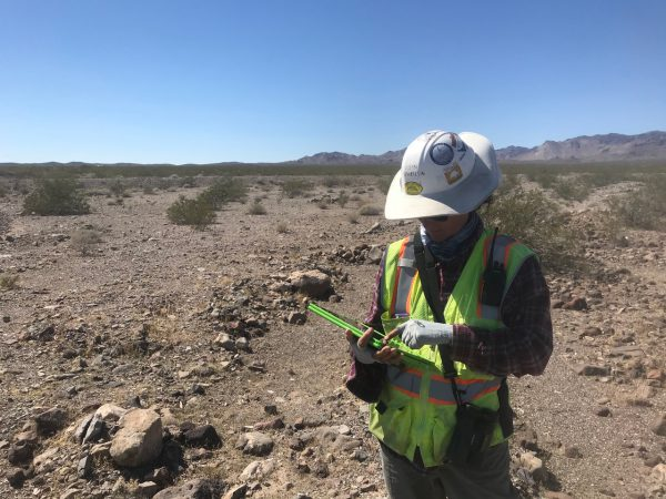 Wildlife biologist enters data on a tablet in the Mojave Desert.