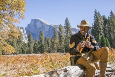 Black man in historical uniform sitting on log holding a flute with a meadow, pine trees and a granite half-dome in the background.