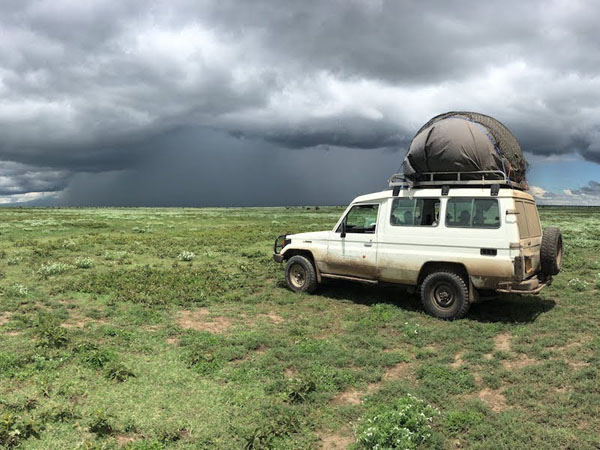 A dirty white Land Rover with large, gray balloon-like object used for wildlife tracking on top, is parked on grassy plain with dark clouds and heavy rain in distance.