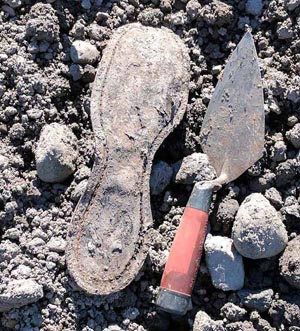 Technology in archaeology in action: old leather boot sole is lying on lumpy dirt, next to a metal trowel with a red handle.