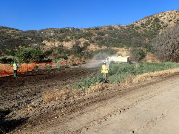 Image of wildlife biologist monitoring excavation and dust abatement at a mitigation bank resoration site.