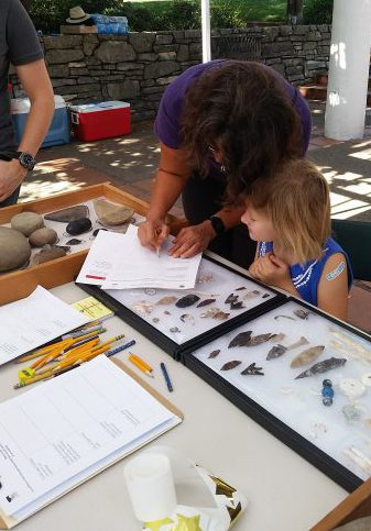 A photo of a woman bending over writing on a piece of paper showing a young girl how to identify and record artifacts next to a case of arrowheads and other cultural resources.