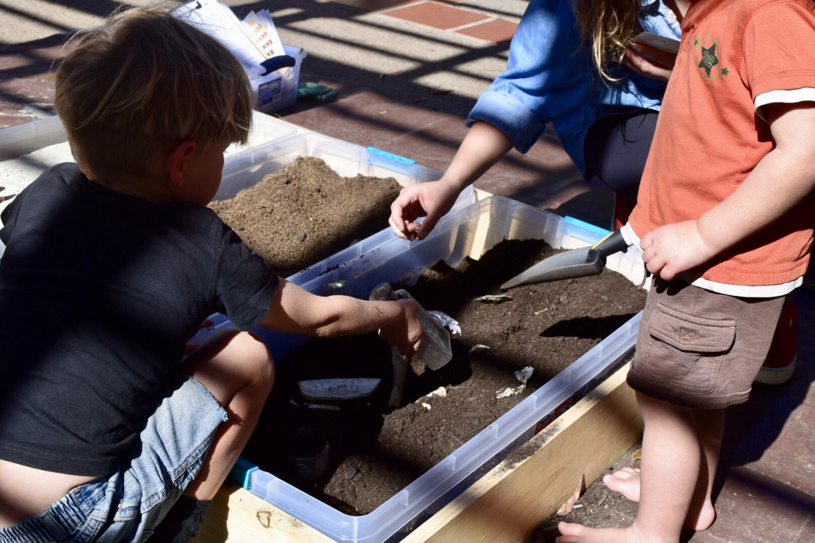 Photo of 2 small children digging with trowels in a large tub of soil to uncover artifacts and simulate excavation
