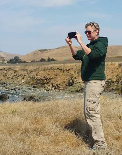 Wildnote CEO Kristen Hazard standing in dry, open country taking photo with mobile phone.