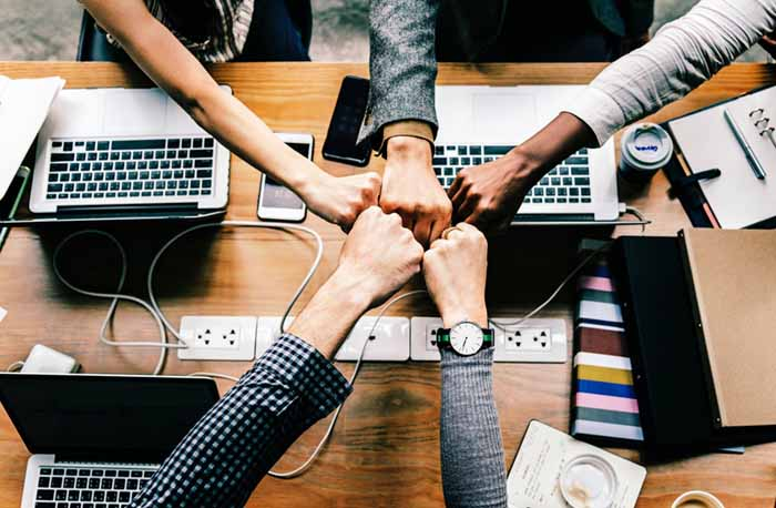 Close up of five knuckled hands of different skin tones meeting together over a desk with laptops in solidarity