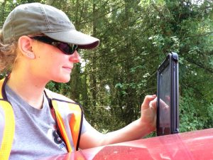 Close up of young woman in cap and sunglasses using tablet for field research.